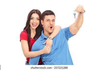 Joyful couple holding a key and gesturing happiness isolated on white background