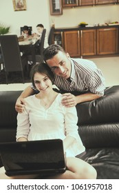 joyful couple relax and work on laptop computer at modern livingroom indoor home
