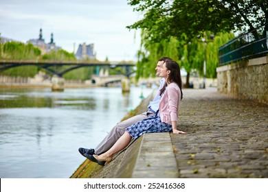 Joyful couple is sitting on the embankment