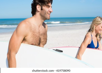 Joyful couple with surfboards walking towards the sea. Young couple running on beach with surfboards under their arms. Smiling young active surfers couple with surfboards on the beach.