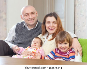 joyful couple together with children at home interior