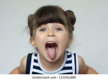 Joyful crazy child gesturing tongues on a white background.