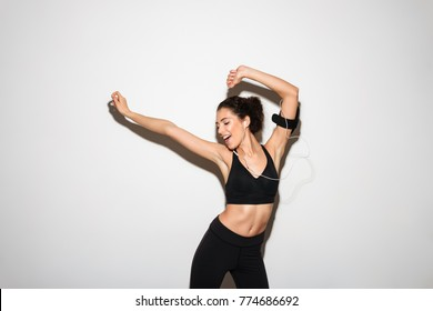 Joyful curly brunette fitness woman listening music by smartphone and dancing over white background