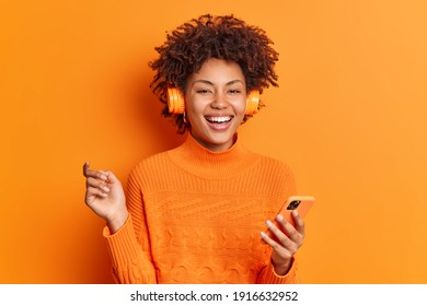 Joyful curly haired woman holds modern smartphone raises hand smiles broadly chooses song for listening from playlist dressed in casual jumper isolated over orange background. Happy emotions