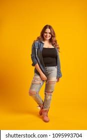 Joyful curvy girl in casual outfit posing at studio