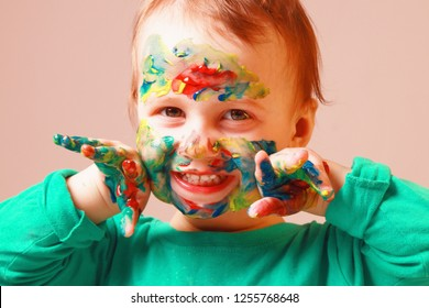 Joyful cute child girl painting. Creativity, make up, child development in art, happy childhood concept.