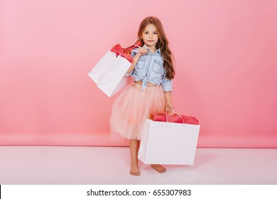 Joyful cute little girl in pink tulle skirt, blue shirt holding packages in hands isolated on pink background. Lovely sweet moments of shopping, happy childhood with presents