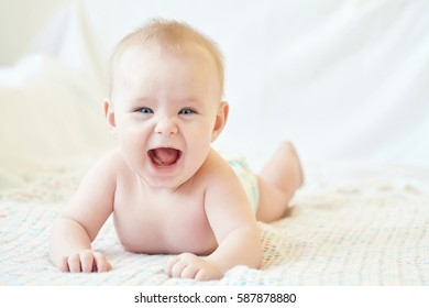joyful cute naked baby on a knitted blanket.