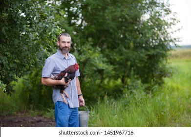 A joyful cute young man holds a rooster in one hand and in the other a metal bucket, the bearded farmer stands on a blurred background of green trees