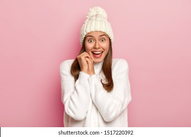 Joyful dark haired millennial girl has happy reaction on good news, smiles broadly, wears warm winter hat and comfortable white sweater, has enthusiastic gaze, isolated on pink wall. Emotions concept