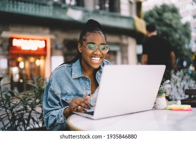 Joyful dark skinned female blogger typing text of publication using laptop computer working remotely, cheerful African American woman in spectacles share positive content and media files on netbook