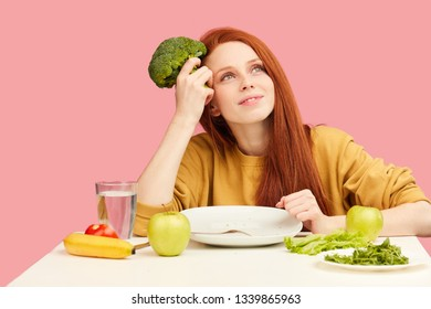 Joyful delighte redhead woman holding broccoli in hands and keeping strict vegetarian diet dreaming of fit and slim body. Weight losing, wellness, low-calorie food, healthy nutrition,dieting concept.