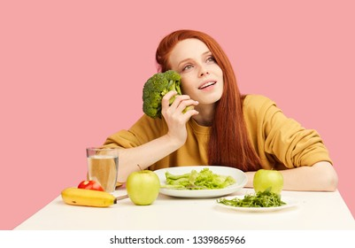 Joyful delighted redhead woman holding broccoli in hands and keeping strict vegetarian diet dreaming of fit and slim body. Weight losing, wellness, low-calorie food, healthy nutrition,dieting concept.