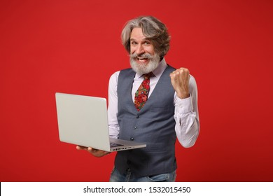 Joyful elderly gray-haired mustache bearded man in classic shirt vest tie posing isolated on red background. People lifestyle concept. Mock up copy space. Hold laptop pc computer doing winner gesture