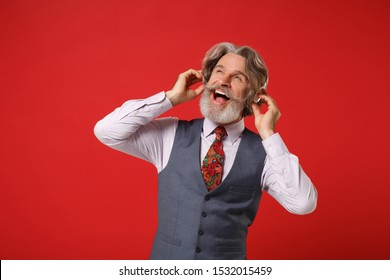 Joyful elderly gray-haired mustache bearded man in classic shirt vest tie posing isolated on red background. People lifestyle concept. Mock up copy space. Listen music with headphones, looking aside