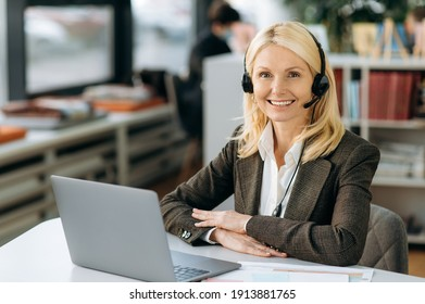 Joyful elegant female operator of call center in headset is looking at the camera, smiling. Intelligent business woman is sitting at the table in office, working in support service, consulting people