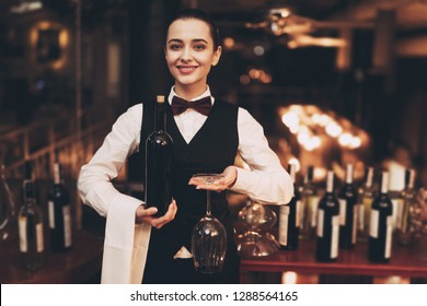 Joyful elegant waitress holding bottle of red wine and glasses, standing near bar. Sommelier tasting wine in restaurant.