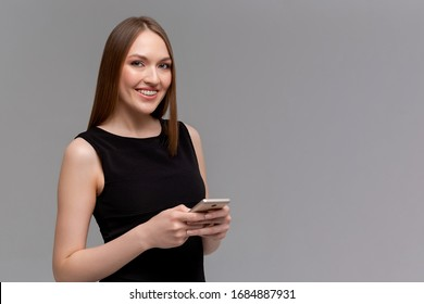 Joyful emotive young european womanwith braces, holding smartphone and smiling cheerfully at camera while retelling interesting article to friend