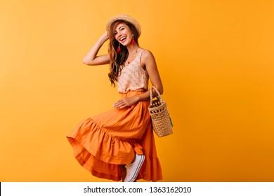 Joyful european lady in summer hat dancing on yellow background. Debonair girl in long skirt laughing while posing in studio.