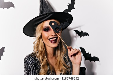 Joyful european woman playfully posing in halloween. Adorable young witch with black makeup expressing happiness.