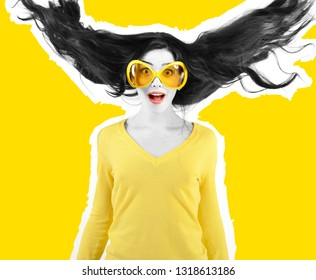 Joyful excited surprised young woman with flying hair and big funny glasses over yellow background. High fashion.
