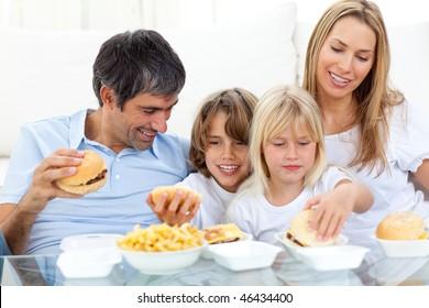 Joyful family eating hamburgers sitting on sofa
