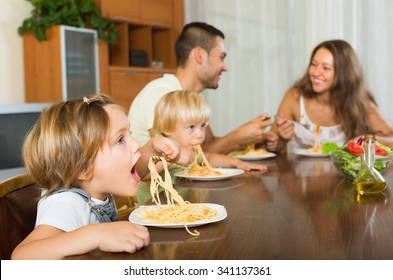 Joyful family of four eating with spaghetti at table. Focus on girl