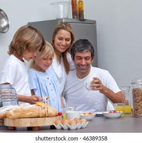 Joyful family having breakfast in the kitchen