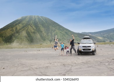 Joyful family jump on volcanic desert, shot outdoors
