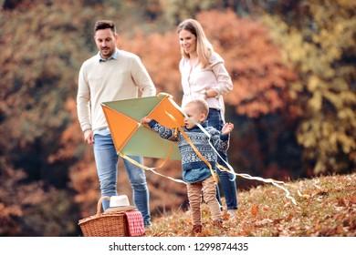 Joyful family picnicking in the park,having fun with kite.