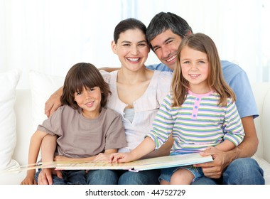 Joyful family reading together on the sofa at home