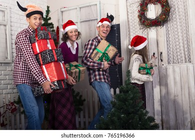 Joyful family, in a Santa hats, goes on a visit for Christmas. Parents and children teenagers, with gifts in their hands, laugh and knock on the door.