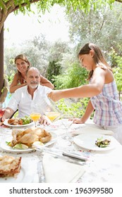 Joyful family sitting at a healthy lunch table in a holiday villa green garden, relaxing during a summer day eating fresh food and enjoying life with child pouring juice. Outdoors eating lifestyle.
