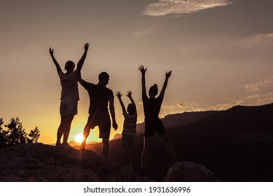 Joyful family of two parents, daughter and young son, raising arms up together. Concept of success, happiness joy of loving people.