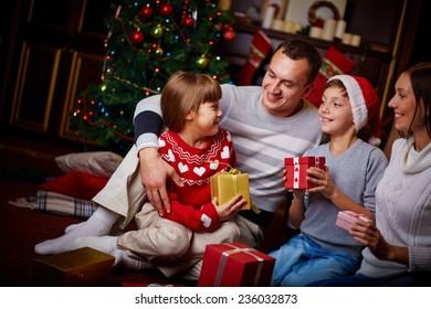 Joyful family with xmas gifts staying at home on holiday eve