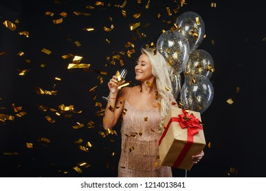 Joyful fashionable young woman in luxury golden dresses celebrating birthday or Christmas party on black background.Having fun, elegant look, smiling. Holding present, gift, golden balloons