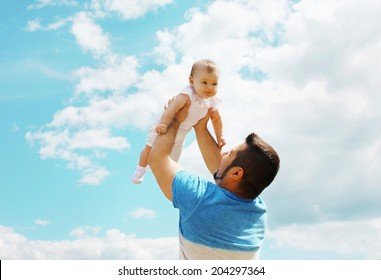 Joyful father and baby having fun in summer day, blue sky
