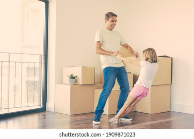 Joyful father playing with daughter among unpacked boxes in new home. Caucasian handsome dad standing in room and holding little girl hands. Family, relocation and moving day concept