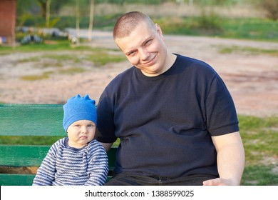 Joyful father sitting with his displeased little son on a bench in the park