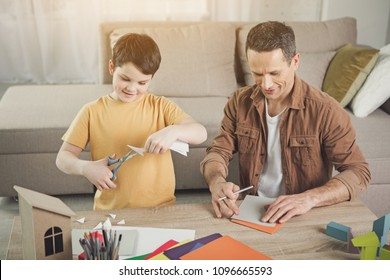 Joyful father and son are making origami together at home. Boy is cutting paper by scissors while man is drawing shape