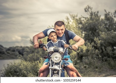 Joyful father son riding motorcycle lifestyle portrait concept happy paternity