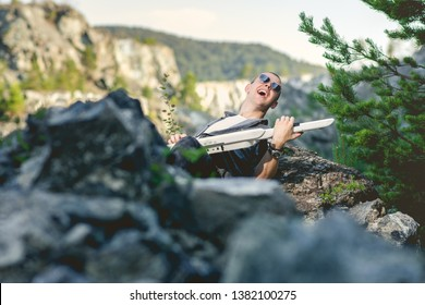 Joyful feeling satisfaction enjoy music musician playing. Relaxed on rocks laying on ground. Young Adult singing and playing musical instrument laying down