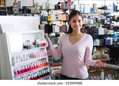 Joyful female customer selecting nail polish from multicolored palette in drugstore
