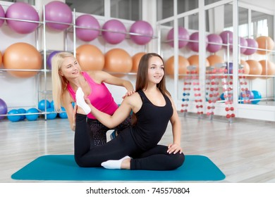 Joyful female fitness trainer smiling at her client while assisting her during stretching copyspace femininity gymnastics aerobics pilates yoga stretch support friendly experienced