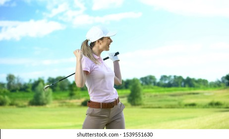 Joyful female golf player with club gesturing yes sign rejoicing successful shot
