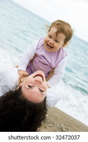Joyful female playing with her daughter on seashore and looking at camera