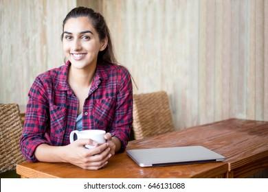 Joyful female student enjoying coffee in cozy cafe