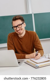 Joyful friendly young teacher with a happy beaming smile sitting work on class notes in front of a green chalkboard