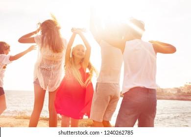 Joyful friends dancing on the beach during sunset