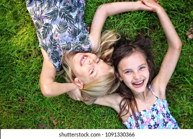 joyful friends lie on the grass and laugh